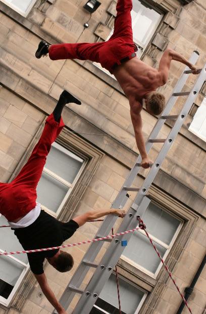men hanging from ladder